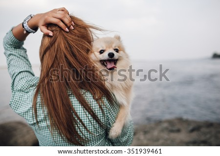 Young adult  woman is holding a dog on her shoulder. Woman turned back  - stock photo
