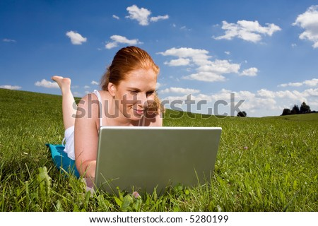 Young adult woman lying on the green grass going to the horizon. With silver Laptop. Above blue sky with clouds. - stock photo