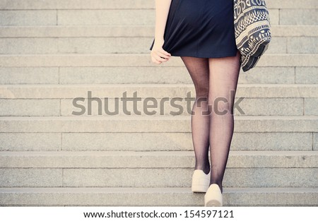 Young adult woman walking up the stairs - stock photo