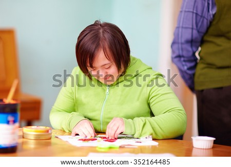 young adult woman with disability engaged in craftsmanship in rehabilitation center - stock photo