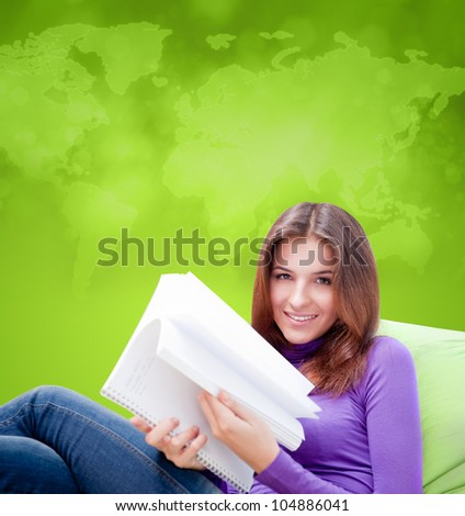 Young adult woman writing in her copybook while sitting on a large beanbag against world map - stock photo