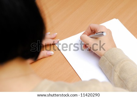 Young adult woman writing on the clean white sheet - stock photo
