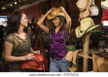 Young adult women trying on cowboys hats in a retail store. Horizontal shot. - stock photo