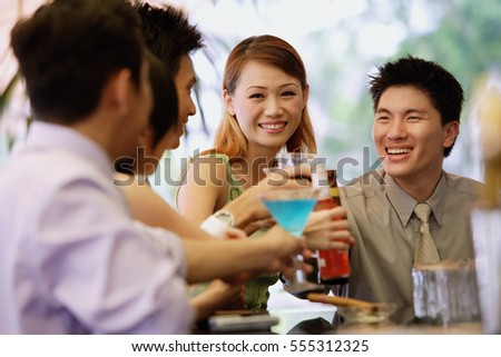 Young adults at bar counter, with drinks