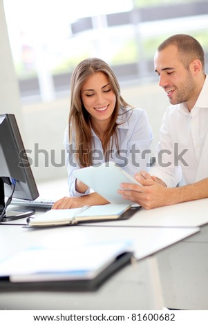 Young adults in training course using touchpad - stock photo