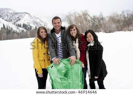 Young Adults in Winter snow sledding - stock photo