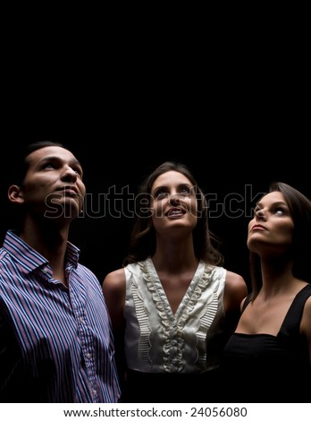Young adults looking up with faith and hope. Space for copy on top. - stock photo