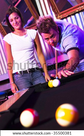 young adults playing pool at nightclub - stock photo