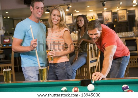 Young adults playing pool in a bar - stock photo