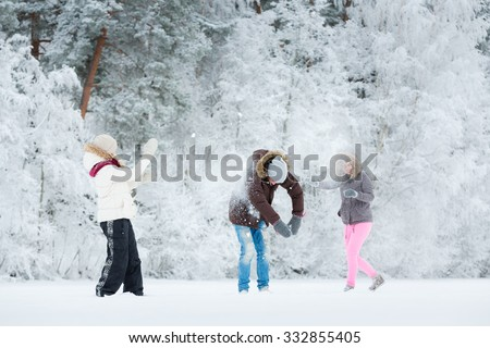 Young adults playing with snow in park in winter - stock photo