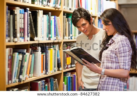 Young adults reading a book in a library - stock photo