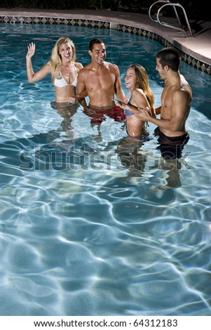 Young adults (20s) having fun in swimming pool at night - stock photo