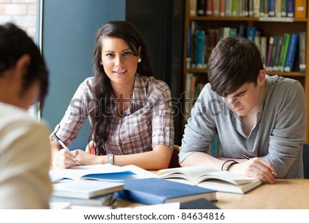Young adults studying in a library - stock photo