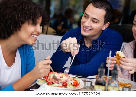 young affectionate couple having lunch in restaurant with friends - stock photo