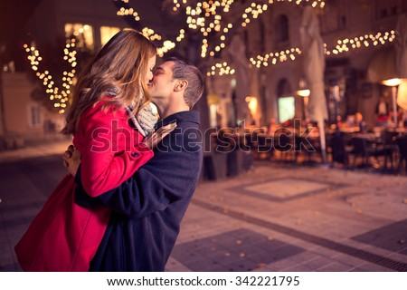 Young affectionate couple kissing tenderly on Christmas street  - stock photo
