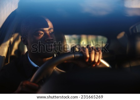 Young affluent successful businessman driving his new expensive car with confidence and pride - stock photo