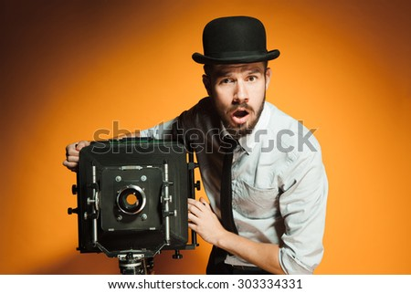 Young  afraid man in hat as photographer with retro camera on an orange background - stock photo