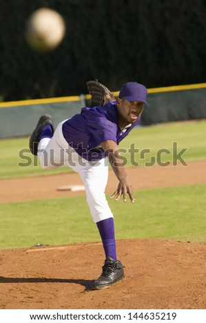 Young African American baseball pitcher throwing the ball - stock photo