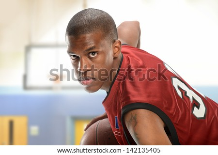 Young African American basketball player playing indoors - stock photo