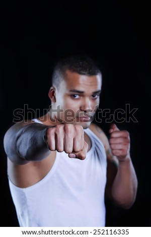 Young African American Boxer screaming isolated on a dark background - stock photo
