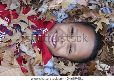 Young African-American boy in seasonal Fall leaves - stock photo