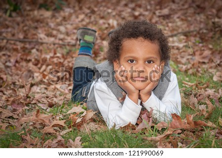 young african-american boy laying on his stomach on the ground looking at camera