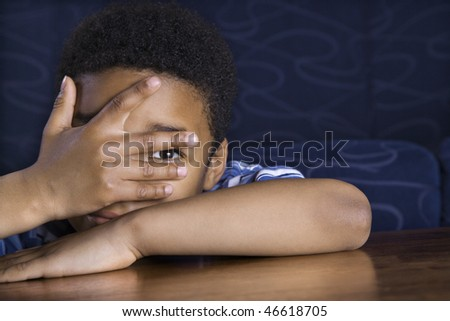 Young African American boy peeks through his fingers as he sits at a coffee table. Horizontal shot. - stock photo