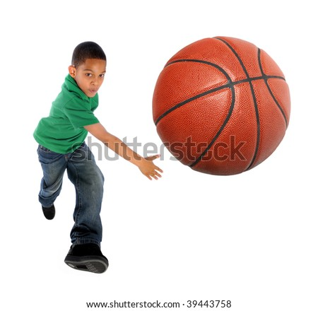 Young African American boy playing basketball - Selective focus on ball - stock photo