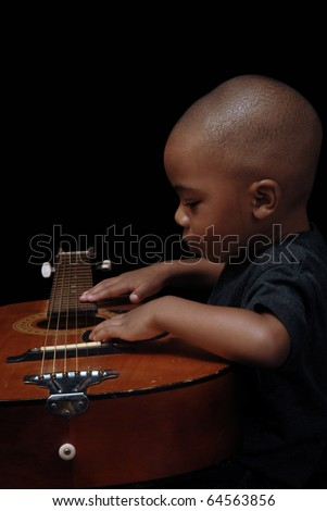 Young African American boy plays and explores the guitar