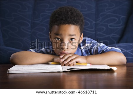 Young African American boy sits on the floor at a coffee table. He is looking towards the camera with his homework on the table. Horizontal shot. - stock photo