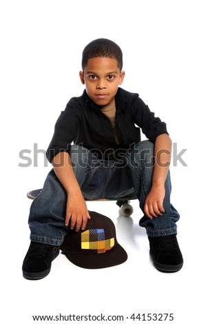 Young African American boy sitting on skateboard isolated over white - stock photo