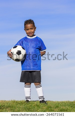 Young african american boy soccer player holding a ball standing on a grass field with a simple blue sky background.  - stock photo