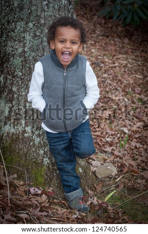 Young african-american boy standing by a tree for his portrait smiling for the camera. - stock photo