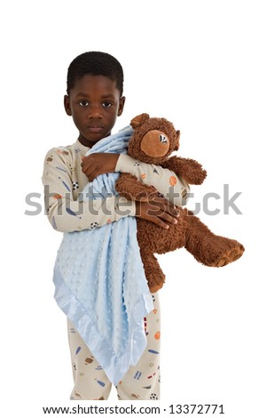 Young African American boy wearing pajamas and holding a blue blanket and a well-loved teddy bear. Isolated on a white background. - stock photo