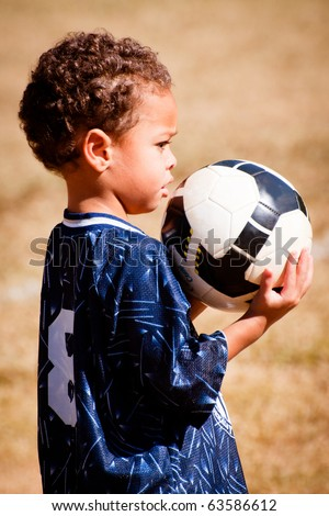 Young African-American boy with soccer ball before game. - stock photo