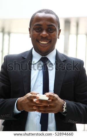 Young African American businessman making a transaction on the phone - stock photo