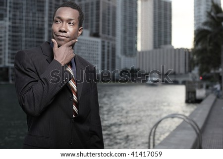 Young African American businessman pondering in the city - stock photo