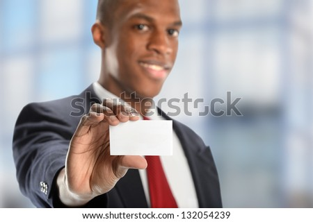 Young African American businessman showing blank card inside building - stock photo