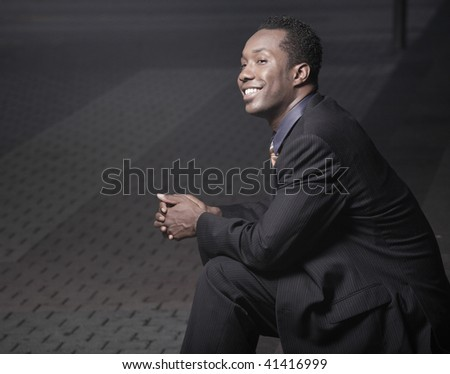 Young African American businessman sitting and smiling - stock photo