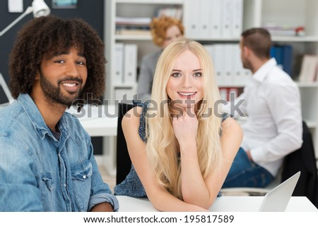 Young African American businessman sitting with a beautiful young blond woman colleague at an office desk as they work together on a laptop - stock photo