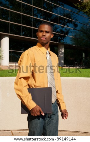 Young African-American Businessman standing outside a building with his laptop