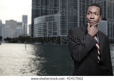 Young African American businessman touching his chin - stock photo