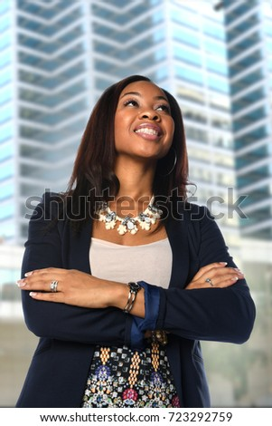 Young African American businesswoman with arms crossed in front of office building