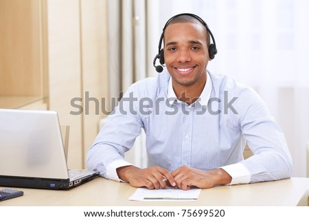 young african american call center consultant with headset in office - stock photo