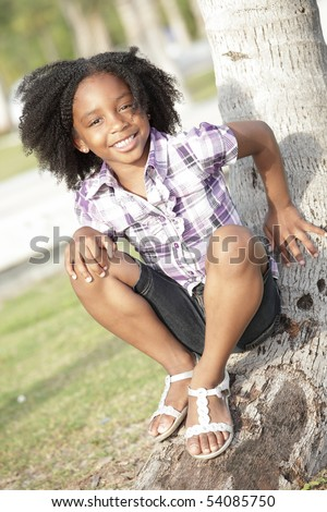 Young African American child sitting on a tree - stock photo