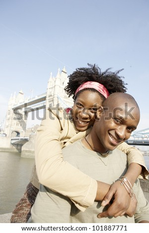 Young african american couple at London's Tower Bridge, hugging and smiling at camera. - stock photo