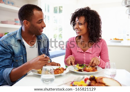 Young African American Couple Eating Meal At Home - stock photo