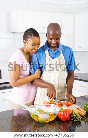 young african american couple in kitchen cooking food