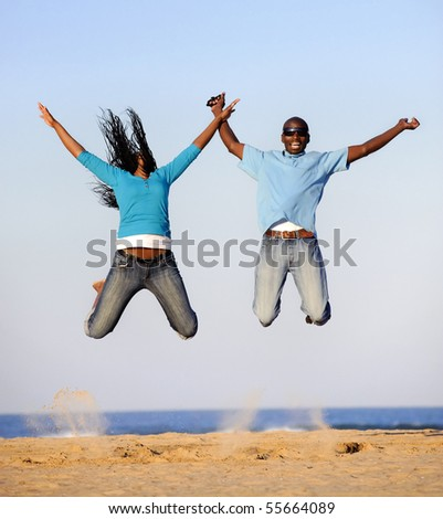 Young African American couple jump on the beach together - stock photo