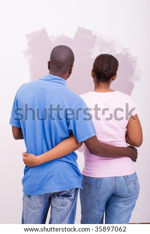 young african american couple looking at new paint on the wall - stock photo